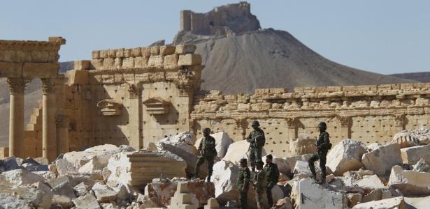 Soldados do Exército sírio patrulham ruínas do Templo de Bel na cidade histórica de Palmira, na Síria