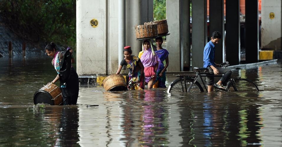 21.jun.2016 - Pedestres e um ciclista tentam atravessar avenida alagada de Mumbai, capital da Índia, que sofre as consequências de um temporal que atingiu a cidade nos últimos dias