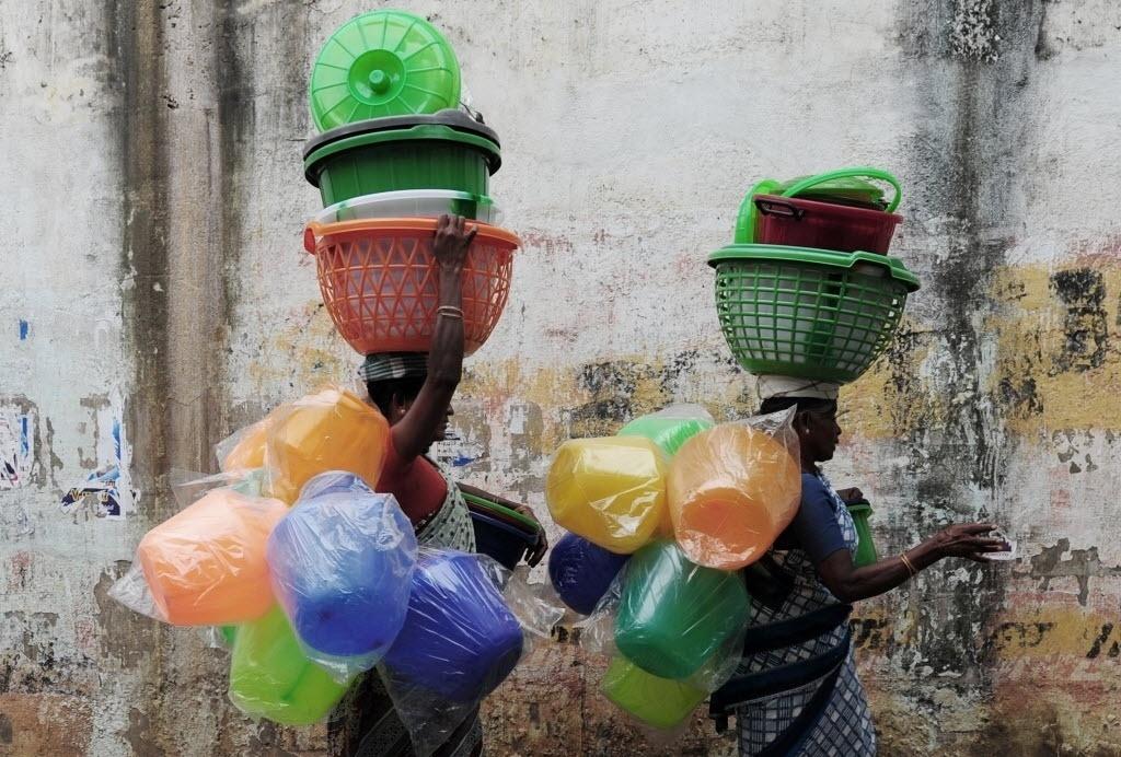 30.jul.2016 - Comerciantes indianas carregam potes de plástico e utensílios para vender em área residencial da cidade de Chennai, na Índia