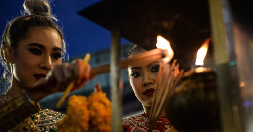 20.ago.2016 -  Dançarinas acendem varetas durante oração em local religioso de Bancoc, na Tailândia