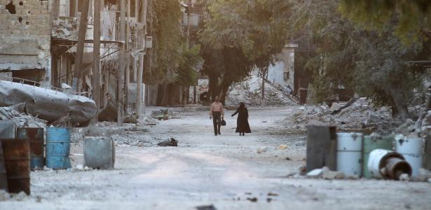 Civis passam por prédios destruídos na área rebelde de al-Myassar, em Aleppo, na Síria - Abdalrhman Ismail/Reuters