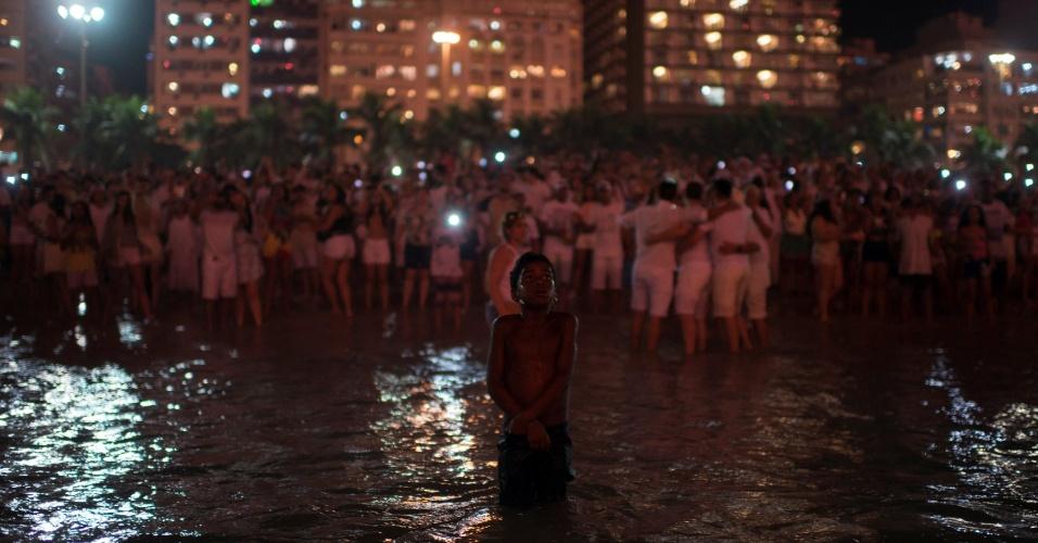 1.jan.2018 - Menino entra no mar enquanto pessoas de abraçam durante as celebrações de Ano-Novo, na praia de Copacabana, na zona sul do Rio de Janeiro