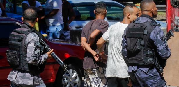 24.mar.2018 - Policiais militares conduzem dois rapazes algemados durante operação na Rocinha - Marcelo Regua/Agência O Globo