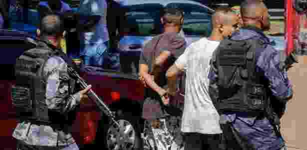 Policiais conduzem rapazes algemados durante operação na Rocinha neste sábado (24) - Marcelo Regua/Agência O Globo