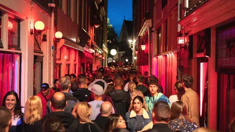 Turistas passeiam por um beco lotado no distrito da Luz Vermelha em Amsterdã - Jasper Juinen/The New York Times