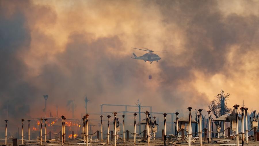 Helicóptero dos bombeiros tenta apagar o fogo na praia de Catania, na Sicília (Itália) - Roberto Viglianisi/Reuters