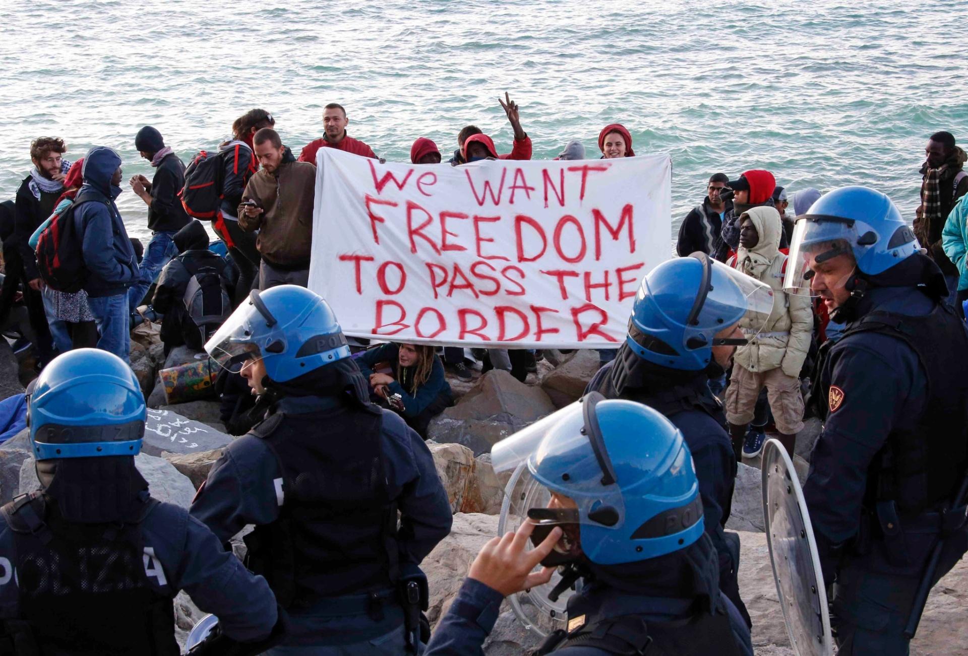 30.set.2015 - Refugiados expulsos de acampamento em Ventimiglia, na fronteira franco-italiana, protestam pelo direito de atravessá-la. Mais cedo, policiais italianos desmantelaram um acampamento de 50 pessoas pela falta de pagamento de eletricidade e de água. O grupo se instalou em uma área de costa com a ajuda de ativistas