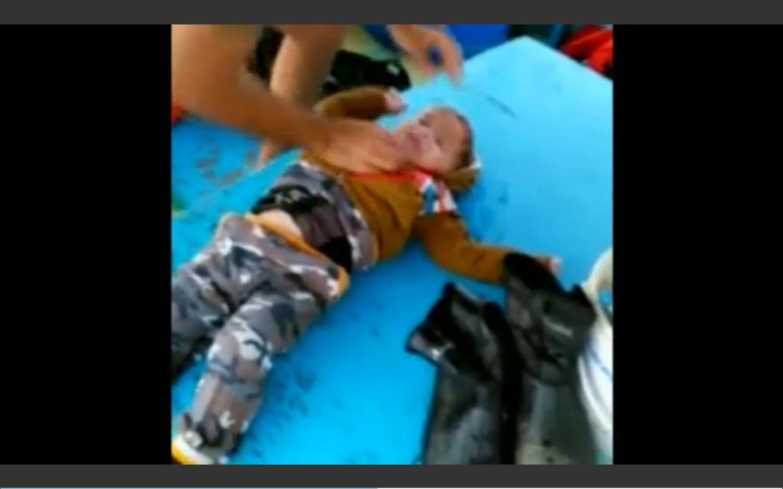 21.out.2015 - Pescadores turcos Cenap Gumran e Recep Evran salvam bebê sírio Mohammed Hasan. que boiava sozinho no mar Egeu e foi reanimado pelos dois homens