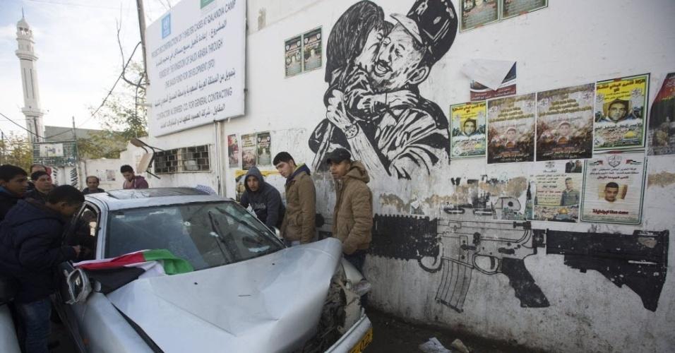 16.dez.2015 - Palestinos olham carro com marcas de tiros disparados por soldados israelenses no campo de refugiados de Kalandia, no norte de Jerusalém. Dois palestinos que estavam no veículo morreram. Segundo o Exército israelense, eles teriam tentado atropelar os soldados