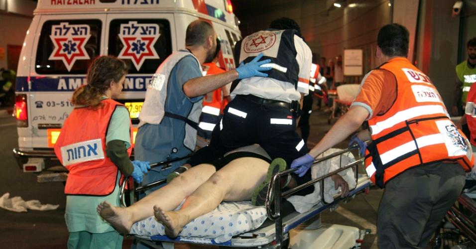 """8.jun.2016 - Médicos israelenses chegam a hospital com pessoa ferida em tiroteio em Tel Aviv, uma das maiores cidades de Israel. Segundo as autoridades do país, três pessoas morreram e outras ficaram feridas durante o ataque que ocorreu  num centro de compras. O porta-voz da polícia israelense Micky Rosenfeld informou por sua conta no Twitter que """"um terrorista"""" foi capturado"""