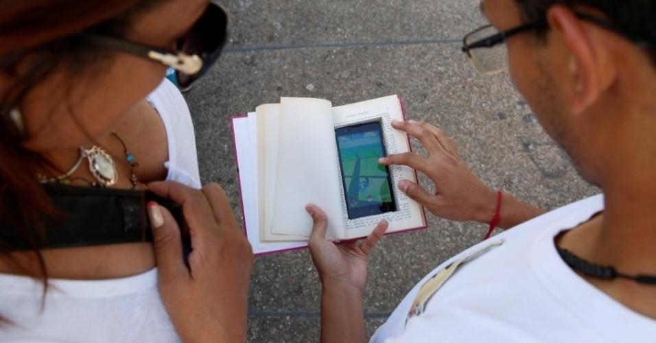 """Com certeza você já deve ter lido várias histórias bizarras que acontecem com quem está jogando """"Pokémon Go"""" distraído no meio da rua. Inclusive, muitos ladrões estão se aproveitando disso. Esse pessoal lá na Venezuela resolveu inventar uma tática para jogar sem ter esse tipo de problema: fizeram um buraco dentro de um livro e colocaram o celular lá. Não é genial?"""