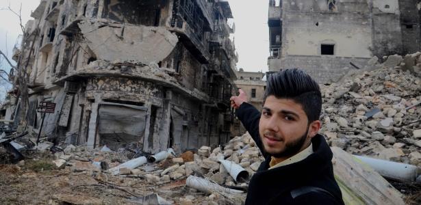 Homem aponta para os destroços do prédio onde morava, em Aleppo, na Síria