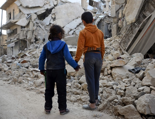 Crianças sírias observam casas em ruínas na cidade de al-Bab