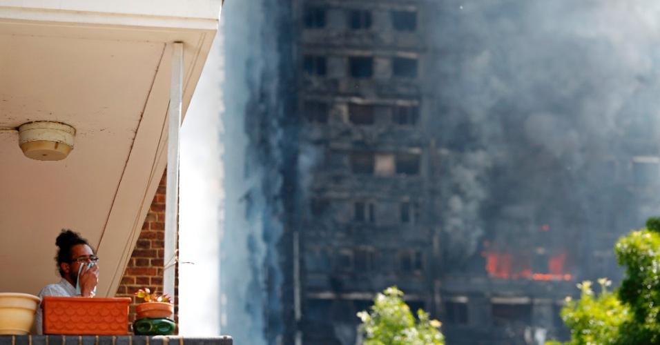 14.jun.2017 - Homem cobre o rosto enquanto prédio Torre Grenfell é consumido pelo fogo, em Londres
