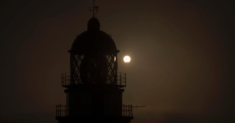 21.ago.2017 - Eclipse solar parcial é visto sobre o farol de Cabo Silleiro, no noroeste da Espanha
