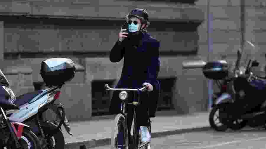 Homem pedala utilizando máscara de proteção para o coronavírus em Milão, na Itália - Xinhua