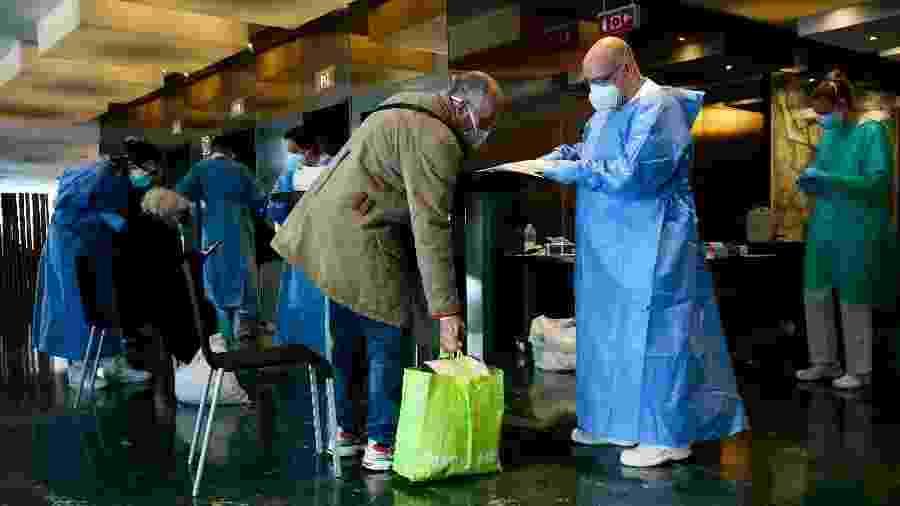 Profissional de saúde recebe paciente que chega ao Hotel Meliá Sarriá - Pau Barrena/AFP