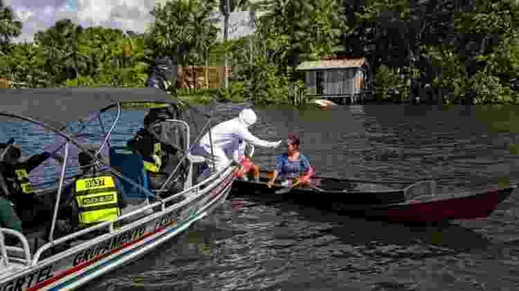 Profissional checa temperatura de mulher na Ilha do Marajó, no Pará - TARSO SARRAF/AFP via Getty Images - TARSO SARRAF/AFP via Getty Images
