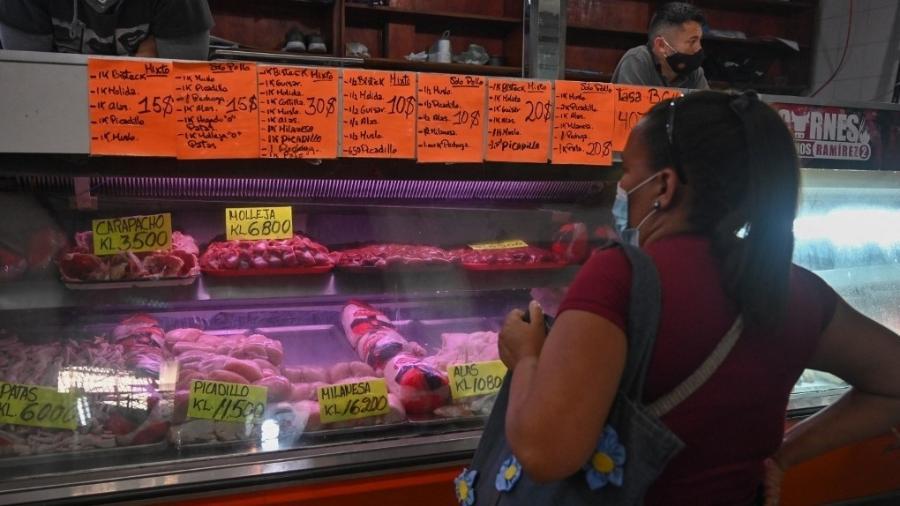 Consumidora observa preços das carnes em um mercado em Caracas, na Venezuela - Federico Parra/AFP
