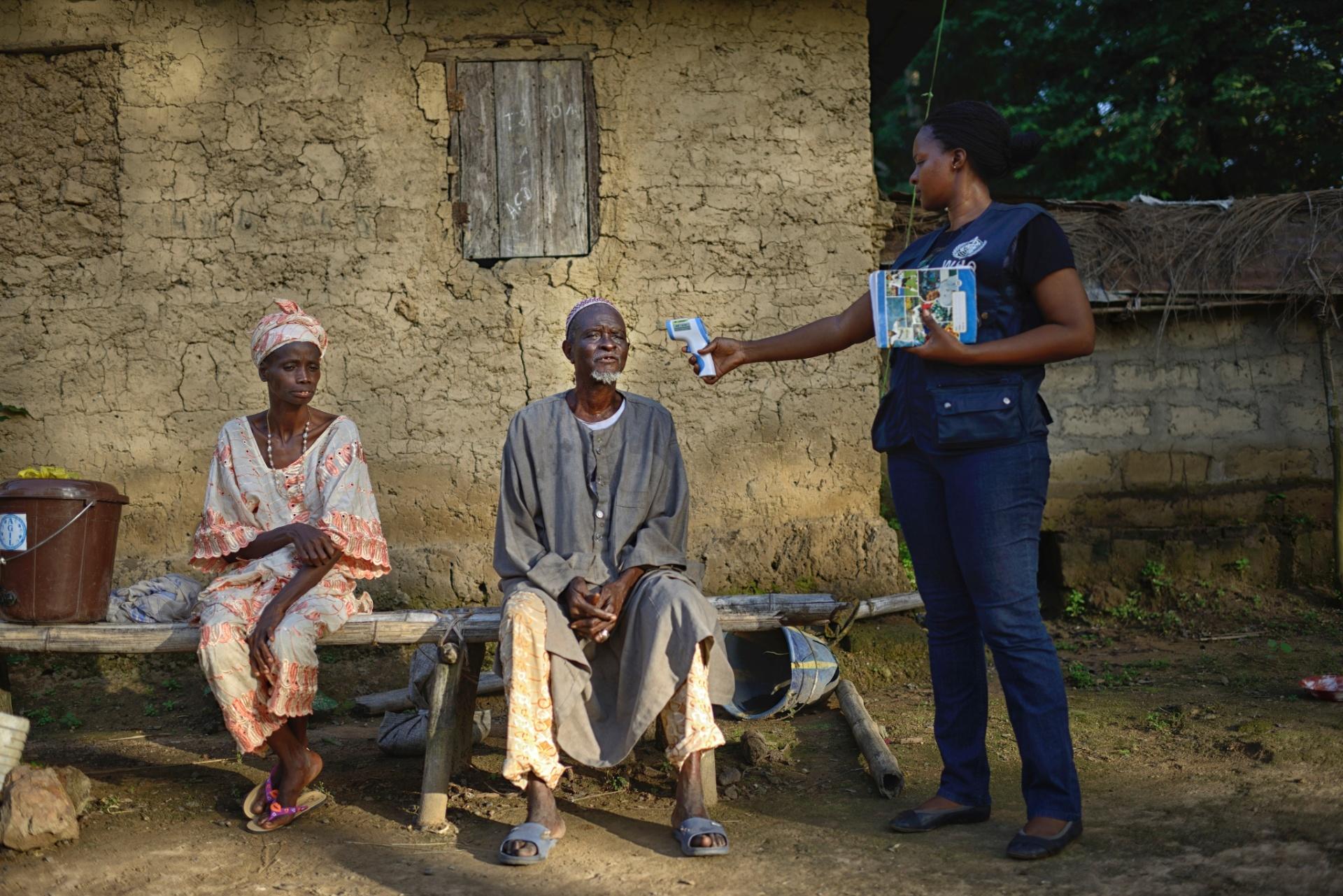 3.nov.2015 - Trabalhadora da Organização Mundial de Saúde mede a temperatura de um homem em Tana, no Guiné, único país do mundo onde o ebola ainda não está extinto