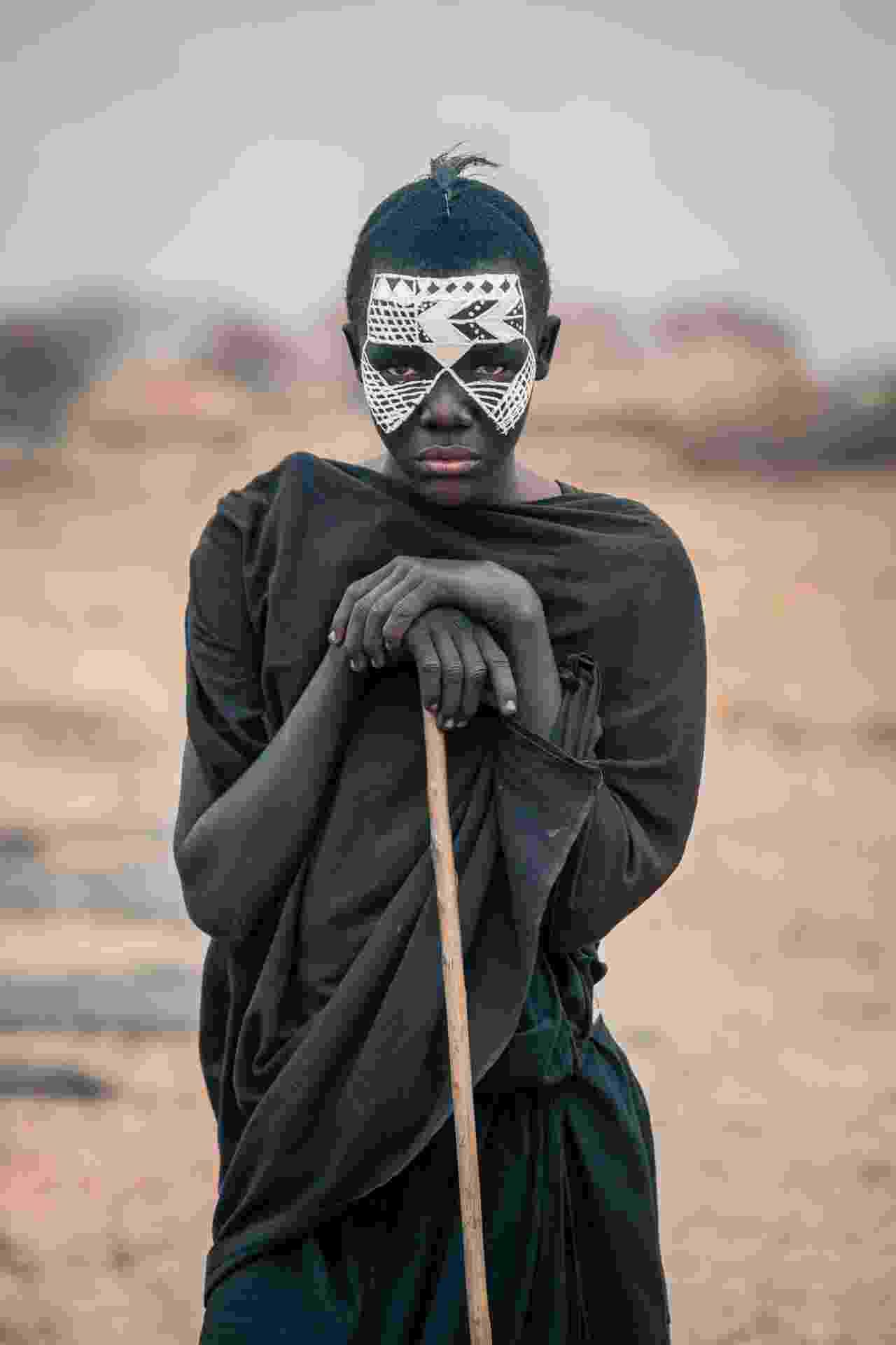 """12.jan.2016 - O garoto da foto é conhecido como Nyangulo e faz parte da tribo masai. A imagem faz parte do ensaio feito em outubro de 2015 pelo fotógrafo romeno Vlad Cioplea, durante expedição à Tanzânia. Cioplea conta que os garotos masai passam por um doloroso processo de crescimento. """"Eles são circuncidados e então têm que deixar suas casas por pelo menos três meses para aprender a sobreviver por conta própria no deserto. Eles devem vestir-se de preto e pintam seus rostos com branco"""", conta - Vlad Cioplea"""