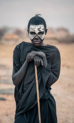 """12.jan.2016 - O garoto da foto é conhecido como Nyangulo e faz parte da tribo masai. A imagem faz parte do ensaio feito em outubro de 2015 pelo fotógrafo romeno Vlad Cioplea, durante expedição à Tanzânia. Cioplea conta que os garotos masai passam por um doloroso processo de crescimento. """"Eles são circuncidados e então têm que deixar suas casas por pelo menos três meses para aprender a sobreviver por conta própria no deserto. Eles devem vestir-se de preto e pintam seus rostos com branco"""", conta"""