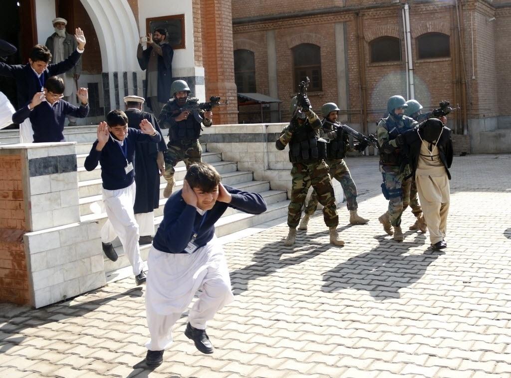 2.fev.2016 - Alunos fogem assustados enquanto soldados do exército realizam um exercício e detêm um homem que interpreta um militante extremista na Escola Colegial Islamita, em Peshawar, no Paquistão