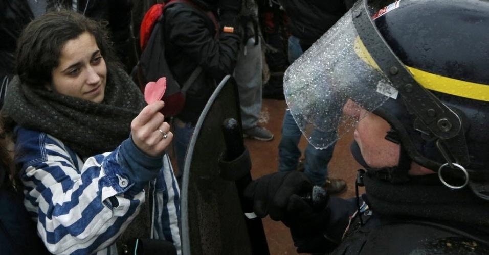 9.mar.2016 - Uma estudante oferece um coração de papel para um policial durante um protesto contra a proposta de lei do trabalho em Lyon, na França. A lei do presidente François Hollande flexibiliza direitos em uma tentativa, de acordo com o governo, de diminuir a taxa de desemprego, atualmente acima de 10%