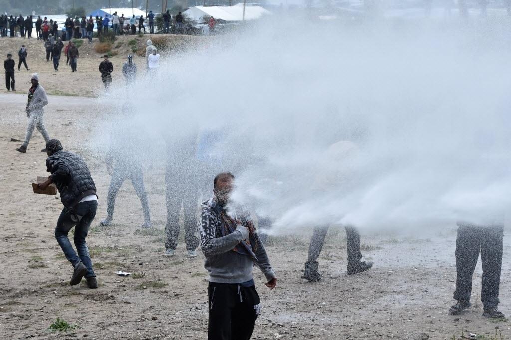 1º.out.2016 - A polícia francesa atirou gás lacrimogêneo e canhões de água contra imigrantes e manifestantes reunidos em protesto no lado de fora de um campo de refugiados próxima a Calais, conhecido como