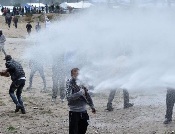 """A polícia francesa atirou gás lacrimogêneo e canhões de água contra imigrantes e manifestantes reunidos em protesto no lado de fora de um campo de refugiados próxima a Calais, conhecido como """"A Selva"""""""