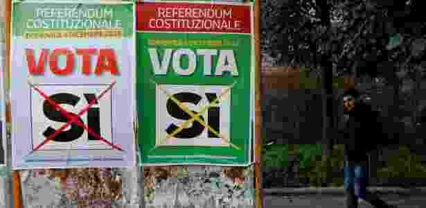 """Homem passa por cartazes que apoiam o voto """"Sim"""" no referendo constitucional de domingo, em Roma, na Itália - Tony Gentile/Reuters"""