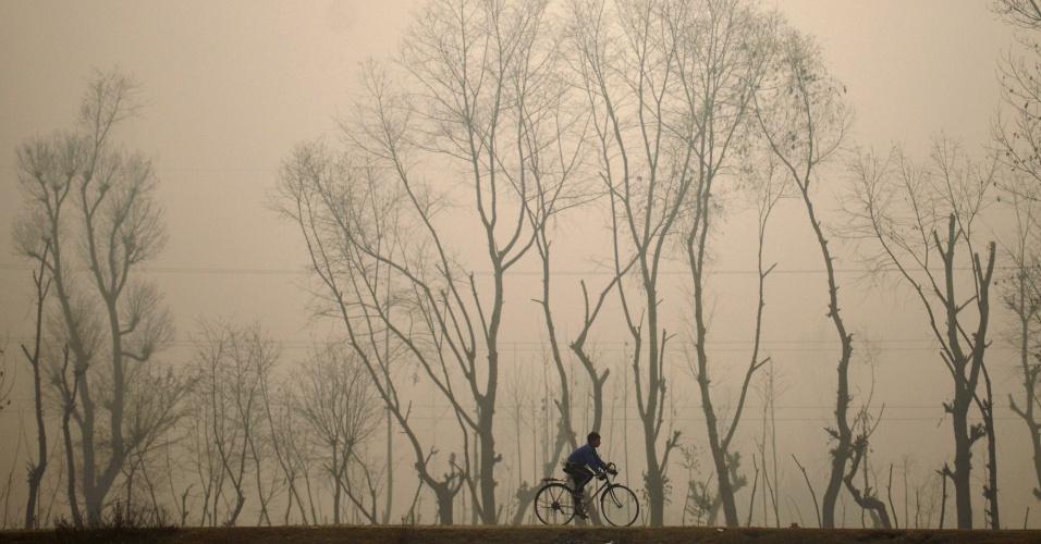 9.dez.2016 - Menino pedala sua bicicleta em dia frio e com forte névoa em Srinagar, na Caxemira (Índia)