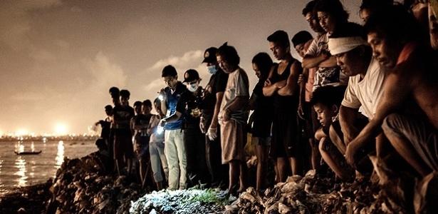 Sobre uma pilha de lixo, moradores do bairro pobre de Tondo, em Manila, olham cadáver de homem que foi morto por esquadrão da morte