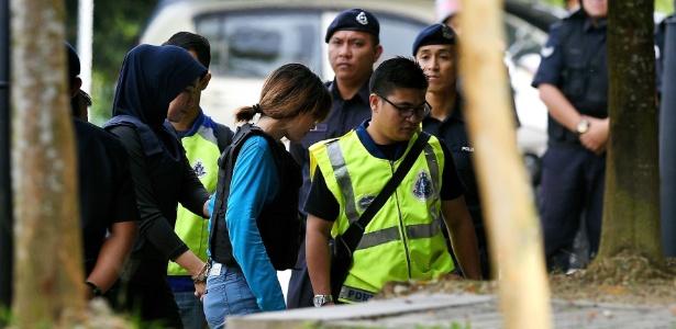 A vietnamita Doan Thi Huong (centro, de azul) é conduzida pela polícia ao tribunal em Kuala Lumpur, Malásia