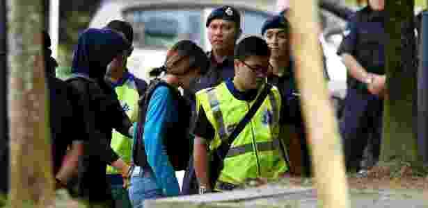 A vietnamita Doan Thi Huong (centro, de azul) é conduzida pela polícia ao tribunal em Kuala Lumpur, Malásia - Manan Vatsyayana/ AFP