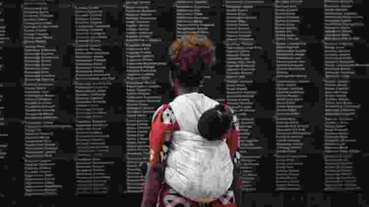 Mulher observa mural com o nome das vítimas do genocídio, que completa 25 anos  - AFP