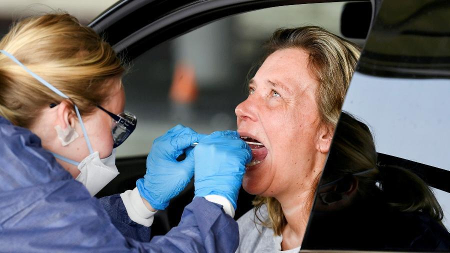 Profissional de saúde colhe amostra de mulher para teste de detecção de Covid-19 em Alkmaar, na Holanda -
