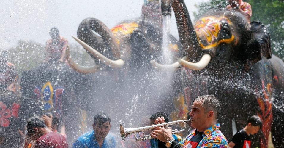 11.abr.2016 - Homem toca trompete enquanto elefantes esguicham água nas pessoas que participam da celebração do Ano-Novo Tailandês na província de Ayutthaya, localizada ao norte da capital Bangcoc