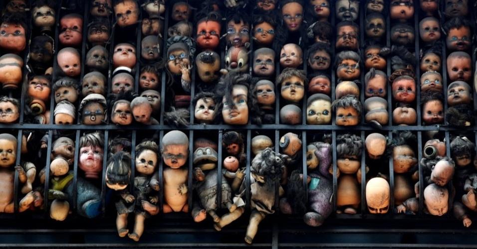 18.jul.2016 - Bonecas são amontoadas em um gradil na varanda do artista e colecionador Etanis Gonzalez, em Caracas, Venezuela