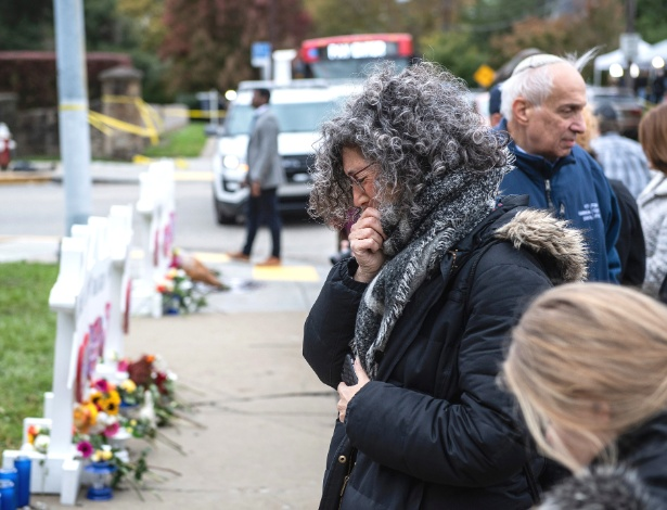 29.out.2018 - Pessoas em luto visitam memorial improvisado em frente à sinagoga onde 11 pessoas foram mortas em um massacre em Pittsburgh - Michael Henninger/The New York Times