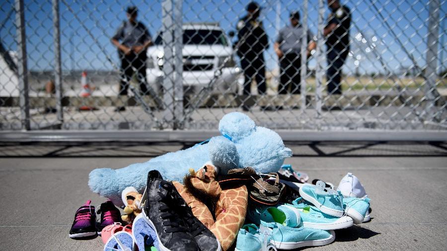 Seguranças parados diante de sapatos e brinquedos deixados para trás no Ponto de Entrada de Tornillo, no Texas, onde os filhos dos imigrantes sem visto foram mantidos após a separação dos pais, em junho - Brendan Smialowski/AFP