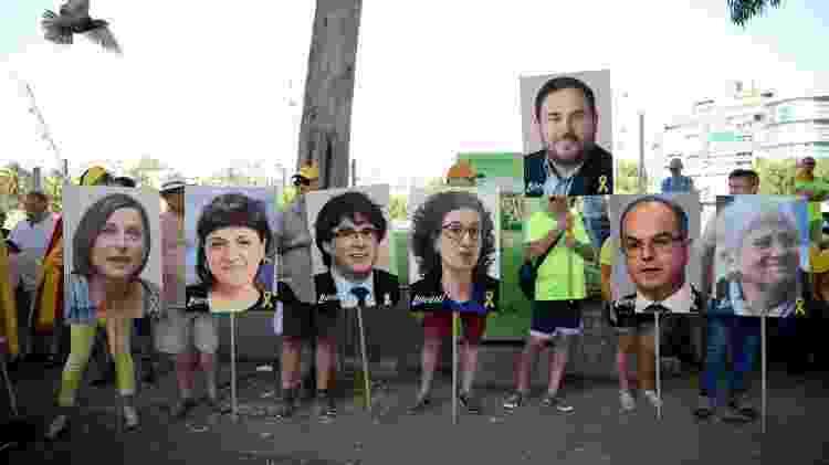 Manifestantes seguram cartazes com as fotos dos líderes catalães presos ou exilados Carme Forcadel, Anna Gabriel, Carles Puigdemont, Marta Rovira, Oriol Junqueras, Jordi Turull e Clara Ponsati durante protesto - Josep Lago/AFP - Josep Lago/AFP