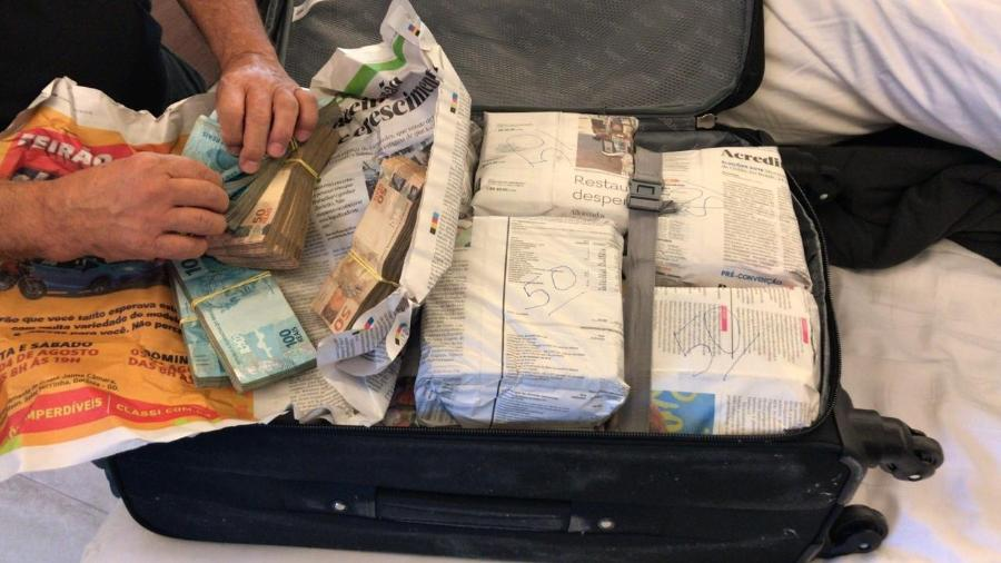 28.mar.2019 - Agentes da Polícia Federal encontraram mala com dinheiro vivo durante o cumprimento de um dos mandados de busca e apreensão - Divulgação/PF