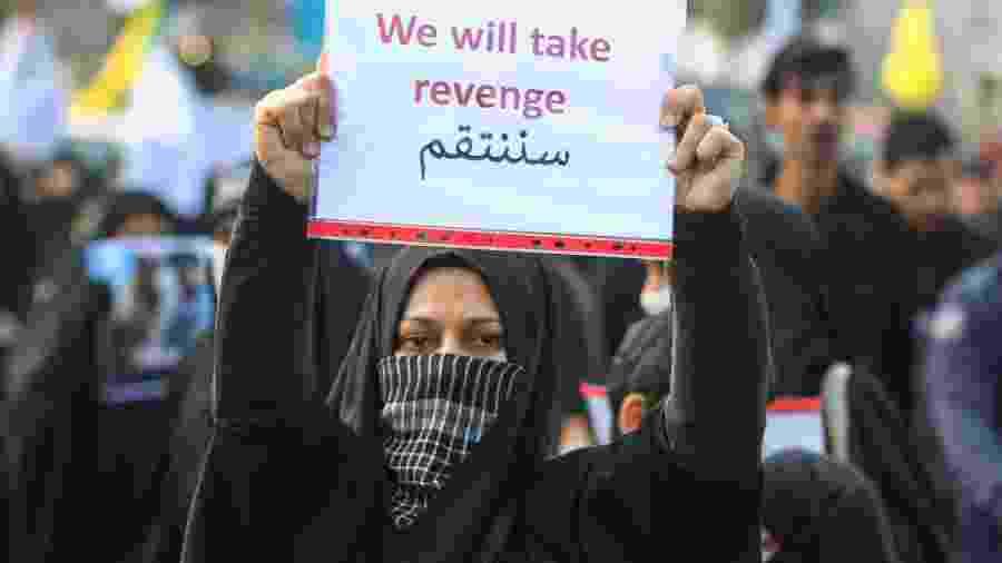 Mulher mostra cartaz que pede vingança contra o assassinato de Suleimani durante o funeral do general iraniano - AHMAD AL-RUBAYE/AFP