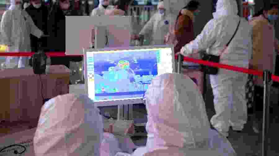 Agentes de saúde usam roupas de proteção enquanto trabalham na análise de um scanner termal na estação de trem de Nanjing -