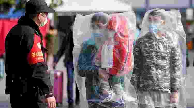 Em Shangai, na China, família se cobre com sacolas plásticas para aumentar a proteção contra o coronavírus - ALY SONG/REUTERS