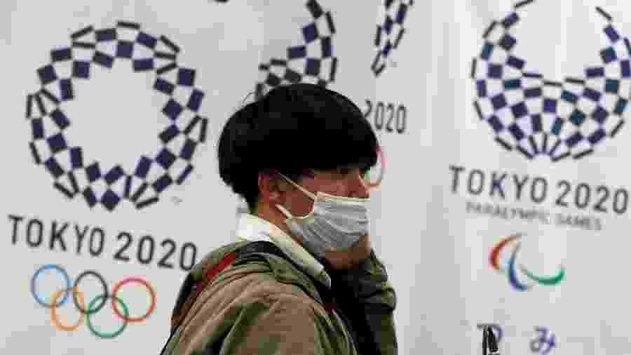 Homem com máscara de proteção em frente à logomarca dos Jogos Tóquio 2020 - ISSEI KATO