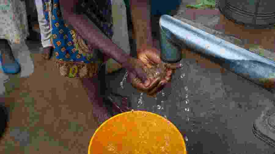 Mulher negra lava as mãos em comunidade pobre - Getty Images