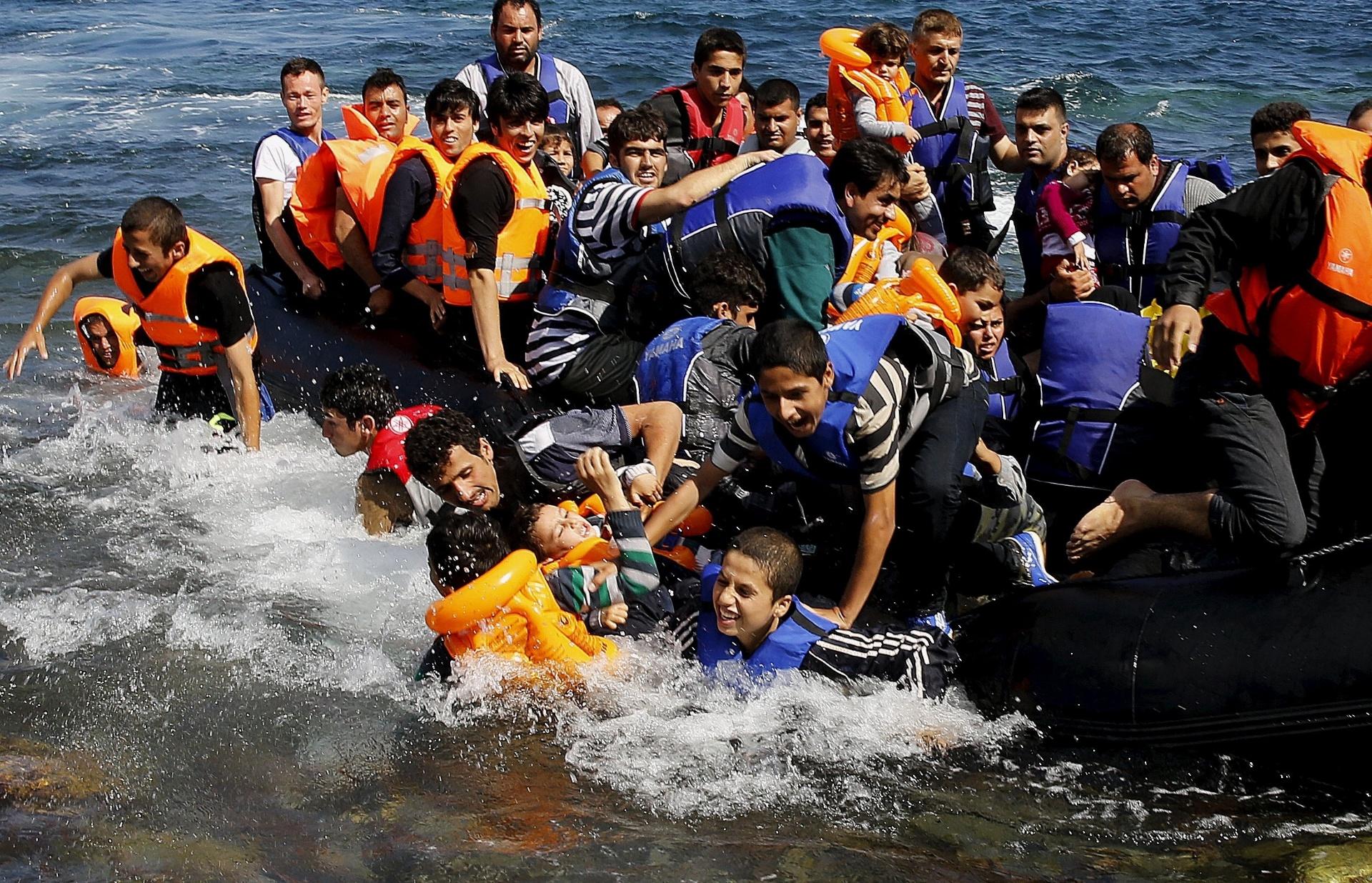 25.set.2015 - Refugiados sírios descem de bote na ilha de Lesbo, Grécia, após cruzarem o mar Egeu desde a Turquia