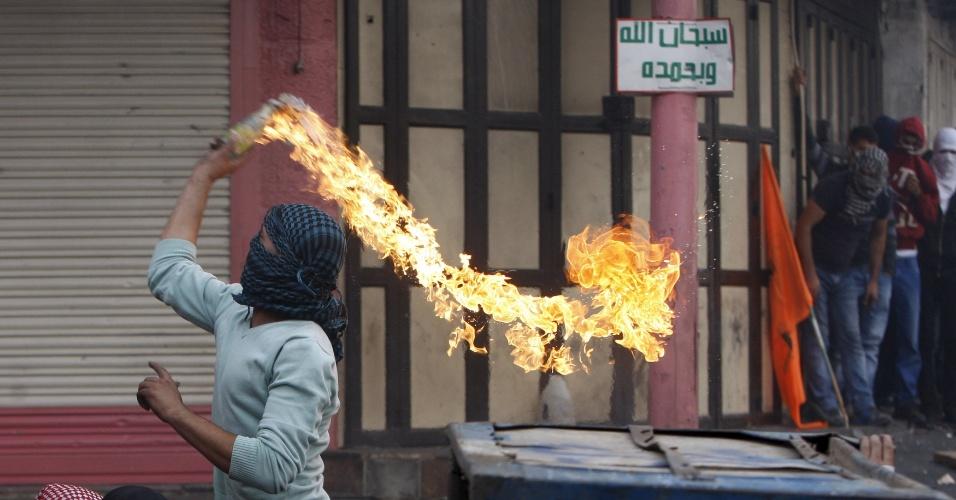 10.out.2015 - Manifestante palestino joga um coquetel molotov contra as tropas israelenses durante confrontos na cidade de Hebron na Cisjordânia. Região sofre escalada de violência nos últimos 11 dias, com confrontos que já mataram quatro israelenses e 17 palestinos - alguns deles baleados pela polícia de Israel